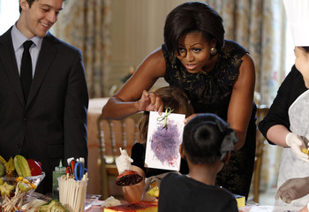 US first lady Michelle Obama shows card made by children at the White House in Washington