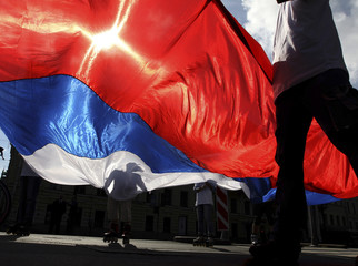 Demonstrators on roller blades carry a huge Russian state flag as they mark Flag day and the anniversary of the 1991 coup in St. Petersburg
