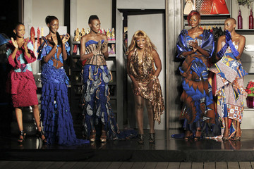 Senegalese designer Gabara walks onto the catwalk beside models wearing her creations after her show during Dakar Fashion Week