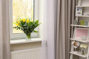 Vase with beautiful tulips on windowsill