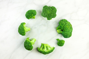 Vibrant green broccoli sprouts on white marble with copyspace