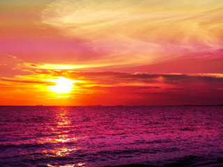 Sunset and cloud on horizon and purple water