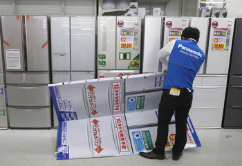 An employee folds a mock model of Panasonic Corp's refrigerator at an electronics store in Tokyo
