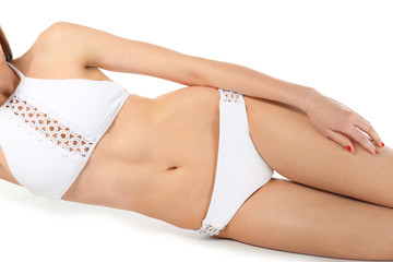 Beautiful young woman in swimsuit on white background, closeup