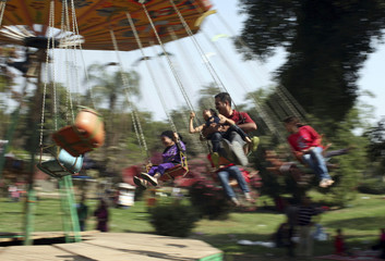 A man sits with his daughter in a swing as they celebrate the spring holiday of Sham el Nessim in Cairo