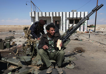 A rebel eats his breakfast as he sits on an anti aircraft gun at a checkpoint on the west of Ajdabiyah