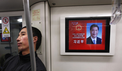 A man travelling on a subway stands next to a screen showing a picture of China's newly elected President and Chairman of the Central Military Commission Xi, in Shanghai