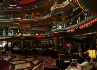 Tourists take pictures in the main Centrum aboard the Royal Caribbean cruise ship Grandeur of the Seas