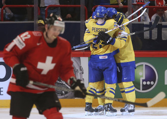 Sweden's players celebrate a goal by Hjalmarsson as Switzerland's Moser skates past during their 2013 IIHF Ice Hockey World Championship final match at the Globe Arena in Stockholm