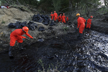Workers try to clean up leaking oil at a stream in Cadereyta
