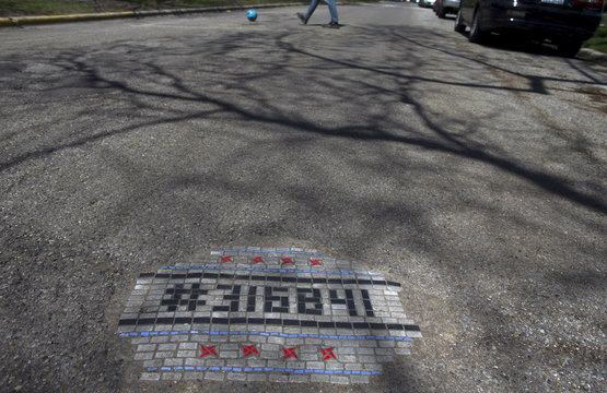 A mosaic art piece created by artist Jim Bachor is labeled with a serial number on a rendering of the city of Chicago flag on a street in Chicago