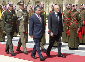 Jordan's King Abdullah and Italian President Giorgio Napolitano review Bedouin honour guards upon his arrival at the Royal Palace in Amman