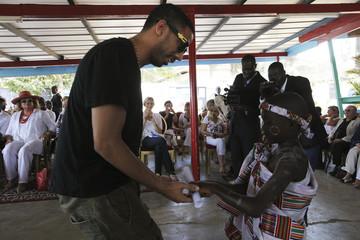 """U.S. music productor and rapper Leslie receives a gift from a child of """"La case des enfants"""" (Box of Children), a shelter for street children, during a fund raising gala in Abidjan"""