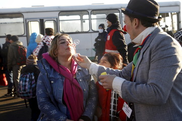 A member of Clown Doctors Red Noses entertains migrants before their departure to Austria at a registration center in Dobova