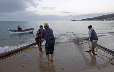 Fishermen pull a net in the seaside village of Sesimbra, south of Lisbon