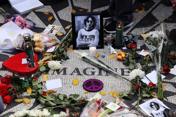 A picture of former Beatle John Lennon is seen among flowers and candles at the Imagine mosaic in the Strawberry Fields section of New York's Central Park to mark the 36th anniversary of his death, in New York