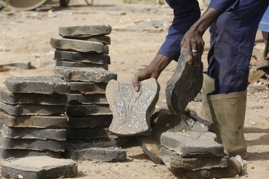 A former rebel of Ivory Coast's civil war works on paver tiles made with recycled plastic as part of the Ivorian government's DDR plan for ex-fighters in Bouake