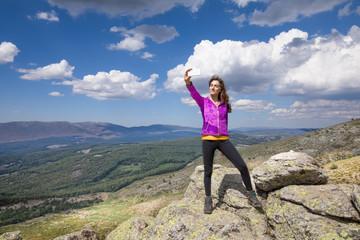 sport hiking or trekking woman with purple jacket, standing on rock peak, with mobile smart phone taking selfie photo picture, behind Lozoya Valley and Guadarrama Park, in Madrid, Spain