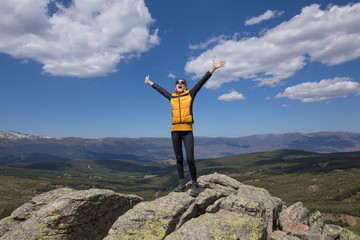 sport hiking or trekking woman with yellow jacket, standing on rock peak, with arms up and screaming open mouth, behind Lozoya Valley and Guadarrama Park, in Madrid, Spain