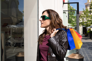 brown hair woman with leather blazer holding shopping bags over shoulder, looking at store showcase in urban street