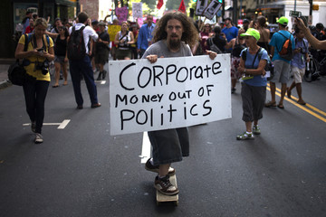 A demonstrator holds a placard while leading a protest from upon a skateboard through uptown Charlotte, the site of the Democratic National Convention in North Carolina