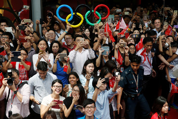 People take pictures with their mobile phones as they wait for Singapore's Olympic gold medallist swimmer Joseph Schooling to disembark the bus during a victory parade in Singapore