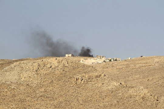 Smoke rises from a Lebanese army base as Lebanese Army soldiers clash with Islamist militants on the mountains next to the entrance of Arsal