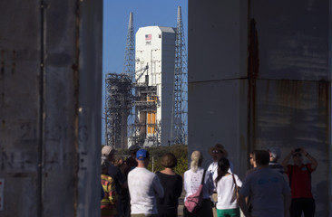 Tourists stand under the original Apollo 1 launch pedestal that overlooks the Delta IV Heavy rocket with the Orion spacecraft on the Space Launch Complex 37B pad at the Cape Canaveral Air Force Station in Cape Canaveral, Florida