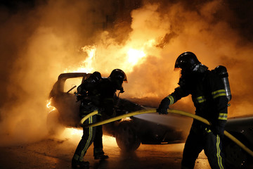 Firefighters extinguish a burning car during New Year's eve celebrations in Lille