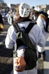 A French midwife, carrying a baby doll, attends a national protest demonstration in Paris