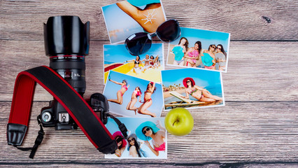 Top view of a lot of photos of cheerful beautiful girls in bathing suits next to a professional camera over a wooden background