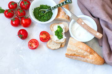 Set of ingredients for bruschettas with goat cheese, pesto sauce and tomatoes abd baguettes on a white stone background. Top view and copy space.