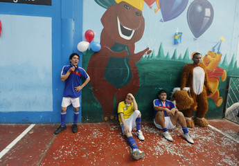 Prisoners, some of whom are wearing jerseys in the colours of France's national soccer team, relax with a team mascot at Lurigancho prison in Lima