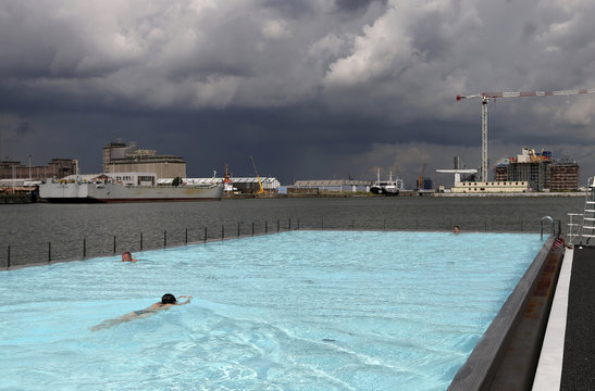 "Swimmers enjoy a floating open-air swimming pool called ""badboot"" in the port of Antwerp"