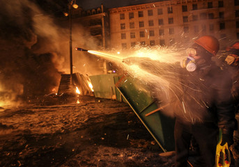 A pro-European integration protester fires off fireworks towards riot police during clashes in Kiev
