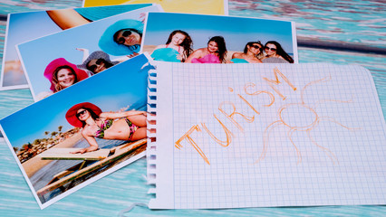 Photos of beautiful girls on the beach and a passport on a wooden table and a piece of paper with a canvas