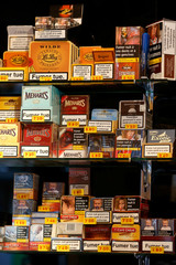 """Packages of small cigars are displayed for sale by a tobacconist with the health warning """"Smoking kills"""" as part of anti-smoking legislation in a French 'Tabac' in Paris"""