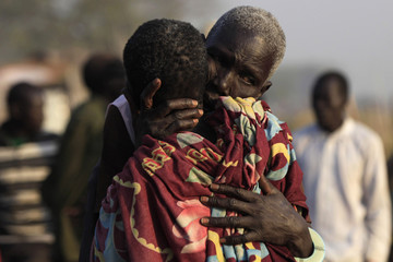 Women displaced by the fighting in Bor county hug each other in the port in Minkaman