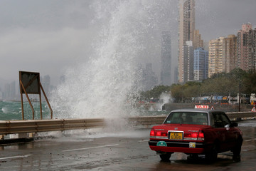 A taxi drives past a big wave on a waterfront as Typhoon Haima approaches in Hong Kong