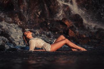 Young woman in white shirt and bikini lies on rock near waterfal