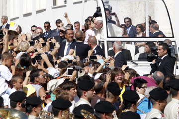 Pope Francis kisses a baby as he arrives to meet the poor and prisoners at the Cathedral of Santa Maria Assunta in Cagliari