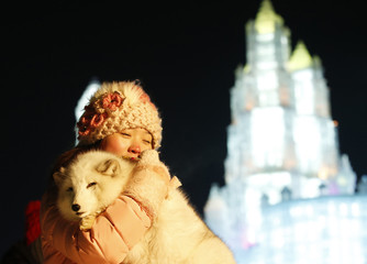 A woman takes her souvenir picture with a white fox in front of ice sculptures illuminated by coloured lights during the opening day of the 31st Harbin International Ice and Snow Festival in the northern city of Harbin