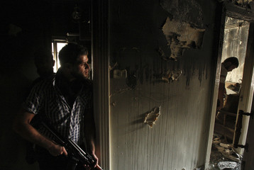 Free Syrian Army fighters carry their weapons as they take positions inside a burnt house in Aleppo's Izaa district