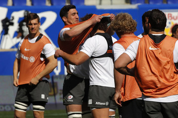 Rugby player Kelly Brown wraps his practice jersey around the head of his teammate Jaques Burger as Saracens held a team practice at Red Bull Arena in Harrison
