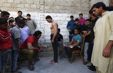 A participant stands on a scale to get signed up for a local bodybuilding and fitness championship in Karachi