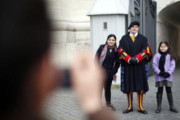Girls pose for a photograph with a Swiss Guard at the entrance of the Vatican