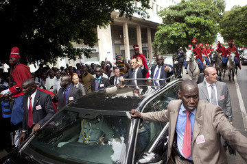 French President Francois Hollande and Senegalese President Macky Sall wave to bystanders in Dakar