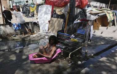 Man takes bath in child's bathtub in front of shack, in a part of Sao Paulo's Luz neighborhood known to locals as Cracolandia