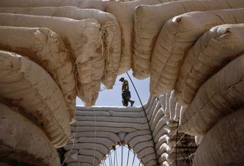 A Palestinian labourer carries buckets on a structure built with sacks of sand in northern Gaza