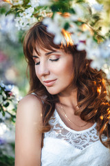 Portrait of a young pretty red-haired woman with closed eyes in a flowery garden, close-up